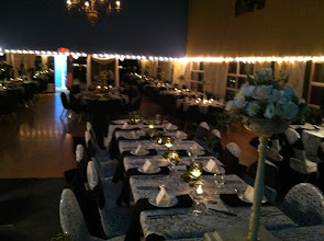 Photo: Head tabke on stage, cream lace overlays over black table cloths Vintage olive glass as votives