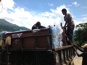 Photo: ...loading furnitures and equipments onto a tractor.