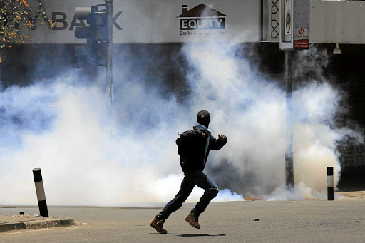 A protester runs away from tear gas during a protest by opposition supporters against the retention of the election officials they blame for last month's botched elections, in Nairobi on October 2 2017. Picture: REUTERS