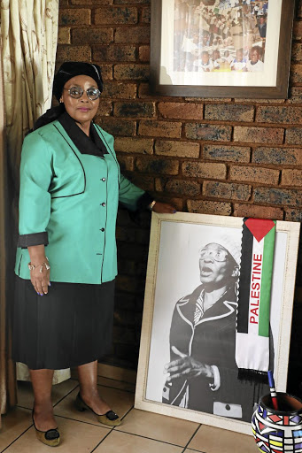 Activist Mmoko stands next to a photo of her relative Pauline Moloise, mother of hanged poet and activist Benjamin.