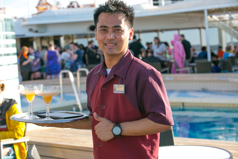 Beverage attendant Godwin Pring brings margaritas to a guest on ms Westerdam.