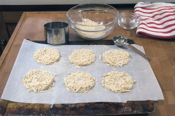 Put a piece of parchment paper on a baking sheet. Add tablespoons of the...