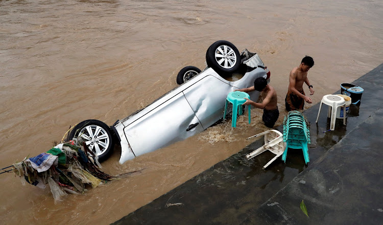 Residents wash chairs next to a submerged vehicle after flash floods brought by continuous monsoon rains in Manila, the Philippines.