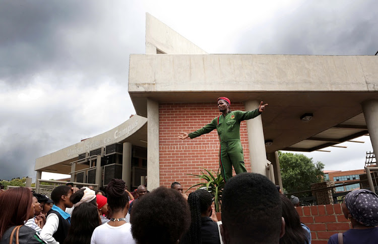 Student representative council undergrad officer Victor Phenyo addresses students outside Unisa's Florida campus in Johannesburg on Monday.