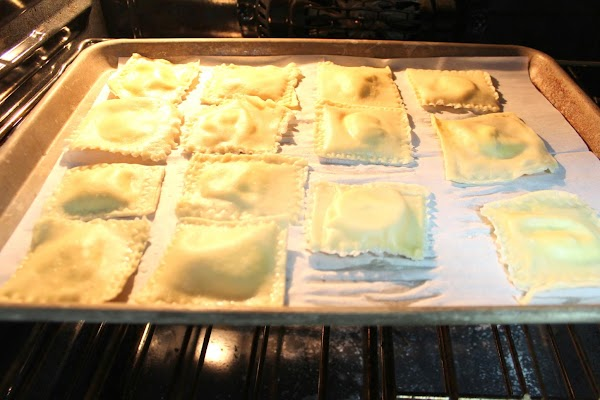 Grease a baking sheet. Place the cooked ravioli on the sheet pan, spray with...