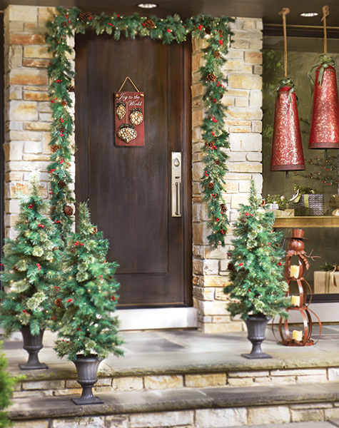 Porch decorated for the holidays with garland hanging over the front door and 3 christmas trees and a snowman and two christmas ornaments.