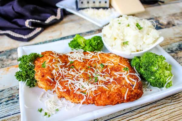 Parm Crusted Chicken Breast With Extra Cheese Sprinkled On Top.