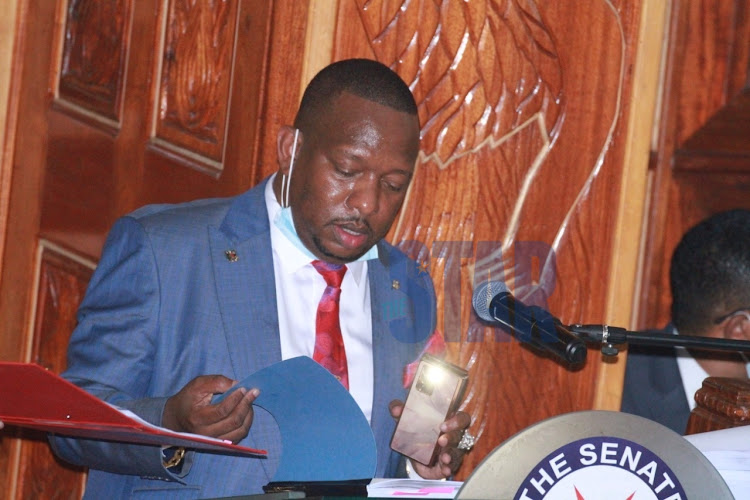 Nairobi Governor Mike Mbuvi Sonko uses his phone torch to read documents at the Senate during the hearing of his impeachment case on December.17th.2020/EZEKIEL AMING'A