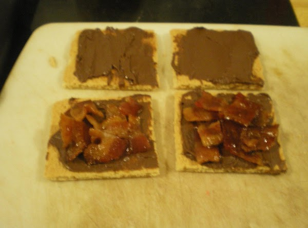 Spread hazelnut spread over graham crackers.  Top half of crackers with bacon pieces.