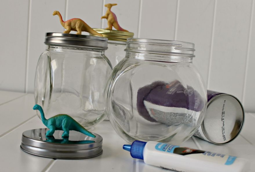 Use adhesive glue or super glue to attach plastic dinosaurs to the top of your jar lids