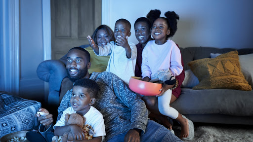 A young family watching TV, with little girl holding the remote.