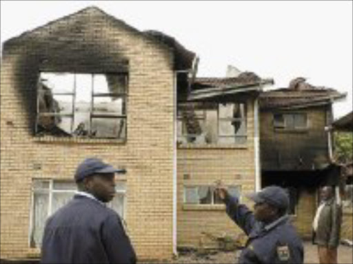 DEATH BY FIRE: Limpopo businessman Elliot Thanyani and police survey the damage to his 15-roomed double-storey house, which burnt at the weekend killing his two daughters. PIc. Elmon Tshikudo.