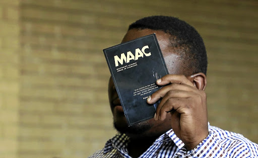 The pastor accused of rape hides his face in the dock at Soshanguve magistrate's court, ironically using material by an organisation opposed to abuse in churches. His alleged victims were boys. / SANDILE NDLOVU