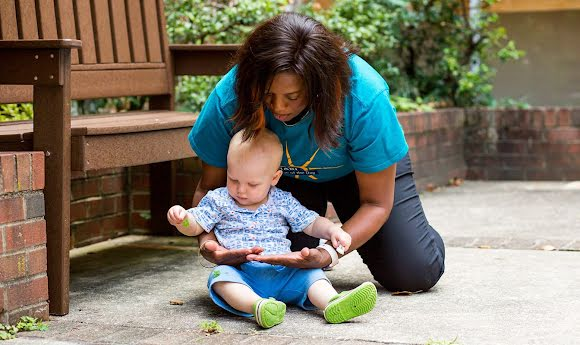 An NDWA-affiliated nanny entertains an infant near a park bench