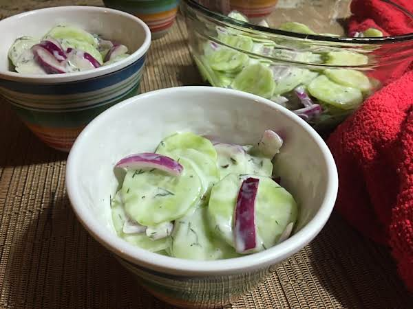 Bowls Of Cucumber Salad Sitting On A Beige Mat Filled With A Red Towel.