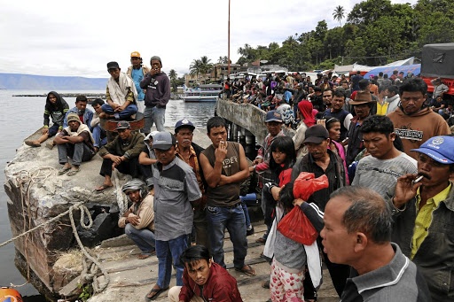 Villagers and relatives wait on a pier at Tigaras port on June 20 for rescue teams to find missing passengers from the ferry accident the previous day at Lake Toba in Simalungun, North Sumatra. Picture: REUTERS