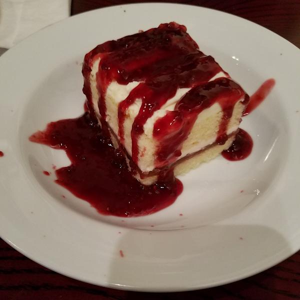 Gluten free white chocolate cake with raspberry sauce.