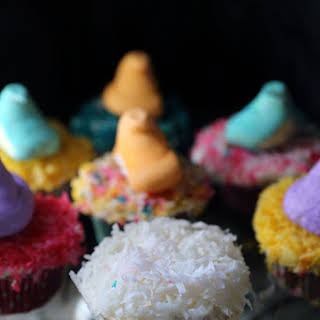 Pineapple Cupcakes with Coconut Buttercream Frosting and Colored Coconut Shavings.