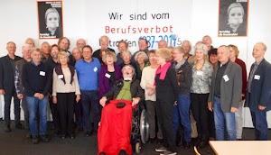 Gruppenbild mit Rollstuhlfahrer. An der Wand: »Wir sind vom Berufsverbot betroffen 1937 - 2015«.