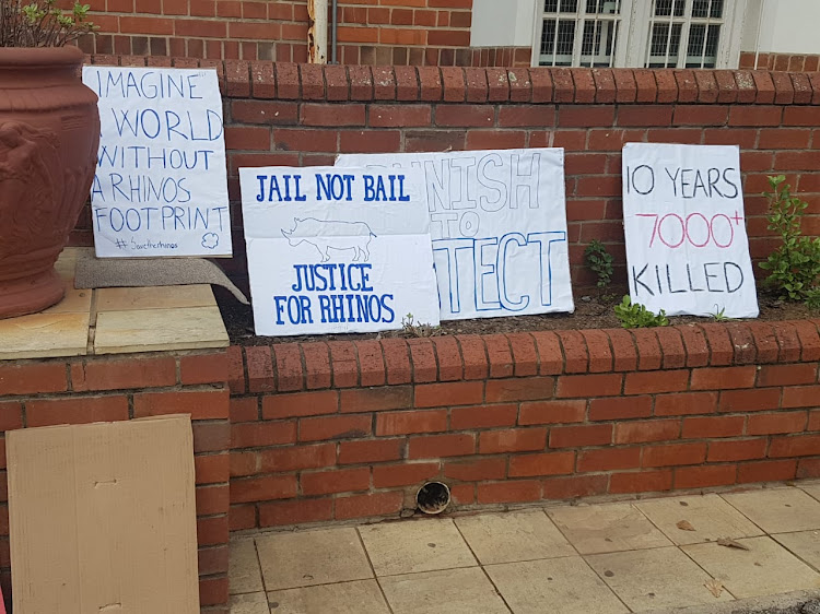 Posters outside the courthouse calling for and end the rhino poaching and harsh sentences for convicted poachers.