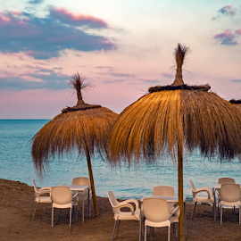Table and chairs with straw umbrella on the beach. at the sunset by Roberto Sorin - Artistic Objects Furniture ( palm, sunshades, empty, bar, view, golden, thermal, nobody, resort, flowers, dining, island, brown, straw, cafe, background, outside, breakfast, ischia, holiday, summer, sea, patio, romantic, cafes, hotel, vacation, exotic, terrace, italy, table, wicker, nature, umbrella, chair, restaurant, shore, abstract, dinner, food, mediterranean, outdoor, tropical, beach, sunset, luxury, garden, travel, forio, villa,  )