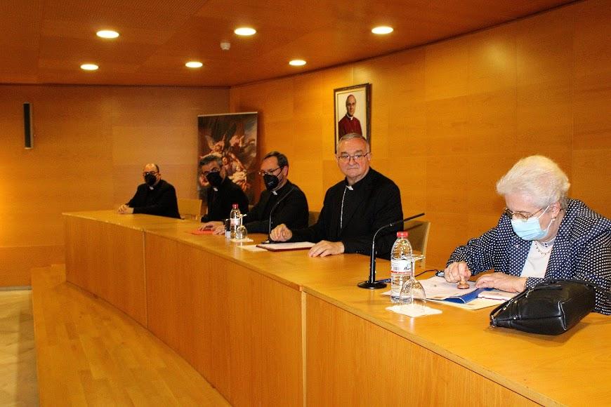 La canciller saliente firmando ante el obispo coadjutor.