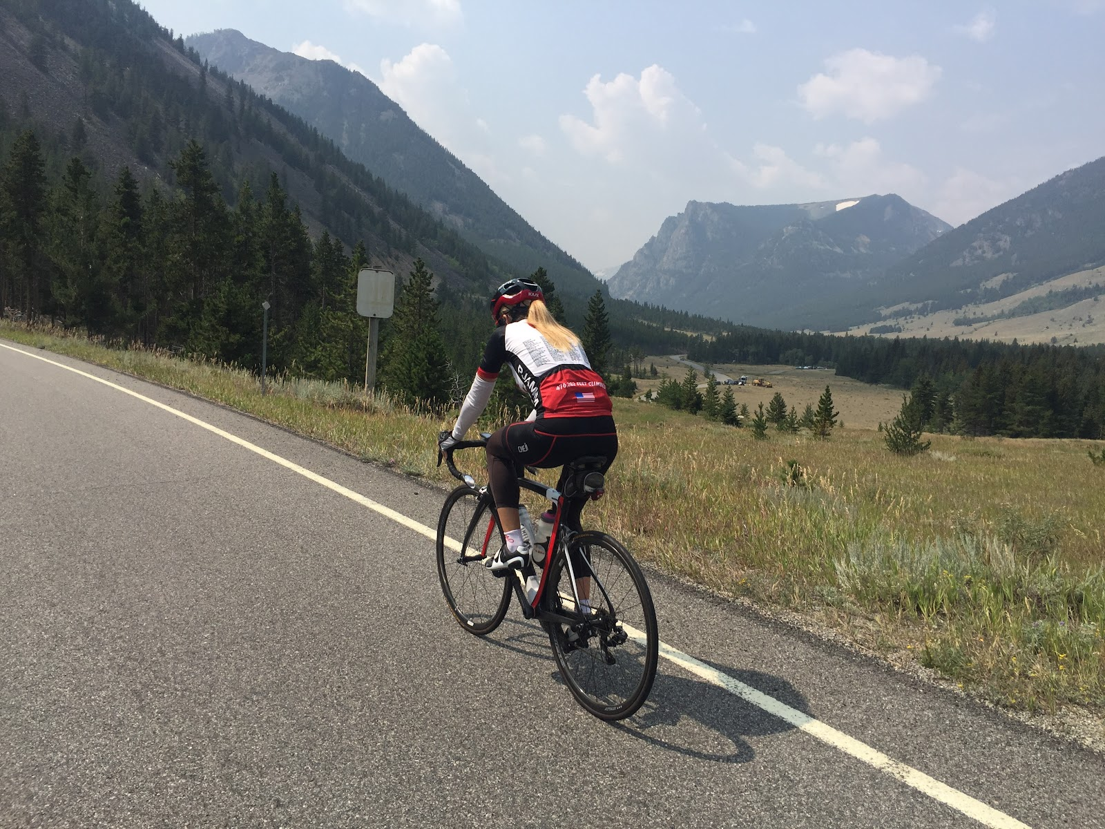 Cycling Bear Tooth Pass North - cyclist on bike on road with valley and mountains in background
