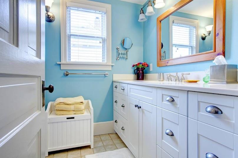 Ściany w łazience pomalowane na niebiesko, a meble drewniane na biało