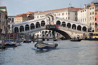 Photo: Poprvé bylo možné překročit Canal Grande suchou nohou přes pontonový most, který postavil roku 1181 stavitel Nicolò Barattieri. Most byl znám pod názvem Ponte della Moneta, pravděpodobně proto, že v blízkosti stála mincovna. Vzhledem k tomu, že díky blízkému trhu, zvaném Rialto, tento most brzy nestačil, byl roku 1255 nahrazen mostem dřevěným. Stavba byla založena na dvou šikmých rampách a pohyblivém středu, který umožnil průplav vyšším lodím.  Nakonec došlo ke spojení s přilehlým trhem a most podle něj dostal své dnešní jméno. Během první poloviny 15. století vznikly dvě řady obchodů po stranách mostu.  Roku 1310, při vzpouře vedené Bejamonte Tiepolem, byl částečně spálen. Roku 1444 nevydržel nápor lidí sledujících průvod lodí a zřítil se. Myšlenka na stavbu mostu kamenného byla poprvé vznesena roku 1503. Současný most, jak ho známe dnes, navrhnul Antonio da Ponte a byl dokončen v roce 1591.