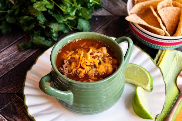 A Bowl Of Famous Taco Soup With Cheese Sprinkled On Top.