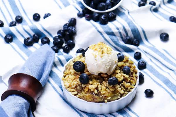 A Bowl Of Blueberry Dump Cake With Ice Cream On Top.