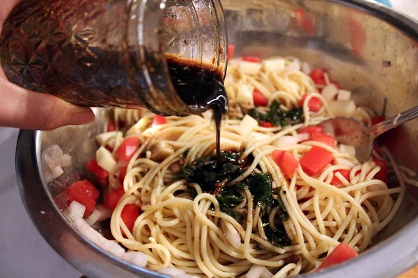 Salad dressing being poured over spaghetti.