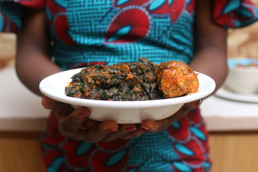 Woman holding a plate of Efo Riro soup