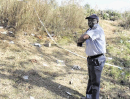 CRIME SCEN: Inspector Moses Maphakela shows where the victim was found.  10/05/2009. Pic. Penwell Dlamini. © Sowetan.
