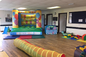 a jumping castle in a hall with soft play equipment in front of it
