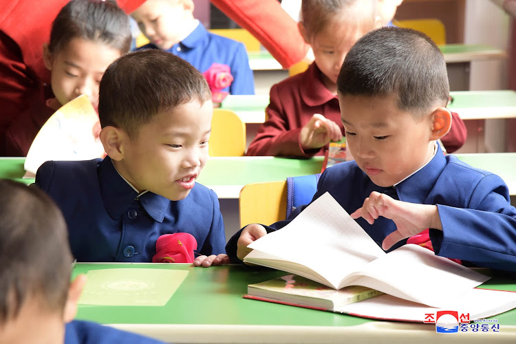 Little boys examine their books as the new school year begins in North Korea.
