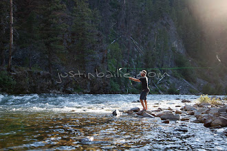 Photo: Man fly fishing while on a raft trip down the Middle Fork of the Salmon River, ID.