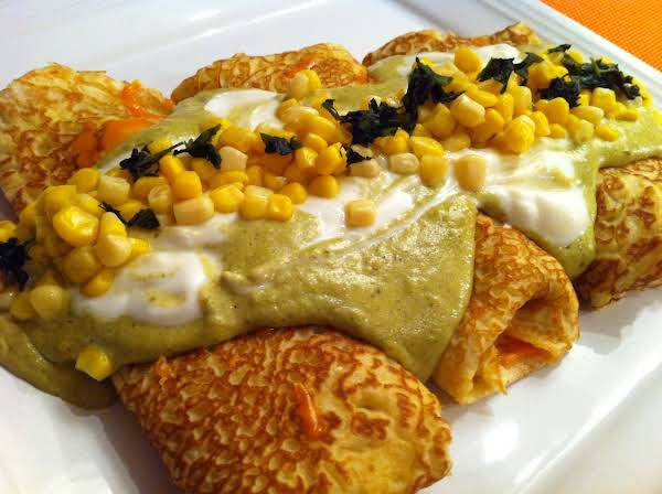 Three Crepes On A White Plate Topped With A Green Sauce, Sour Cream, Corn Kernels And Cilantro.