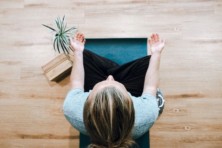 A woman sitting and meditating on a wooden floor with a plant beside her.