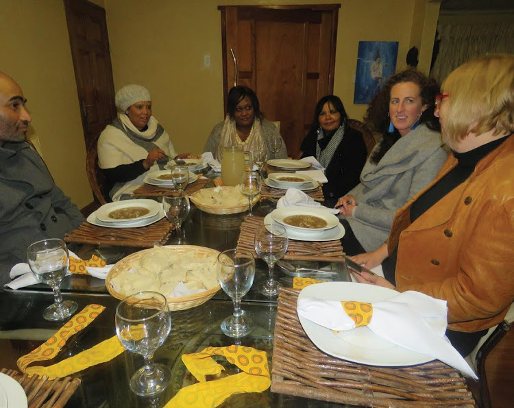 Overseas visitors dine with locals.
