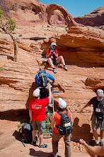Photo: Going up the steel ladder on the second steep section, with Mike and Ann helping people.  Corona Arch is in the background (center, top).