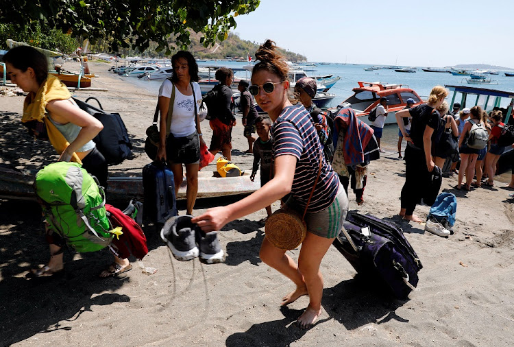 Foreign tourists carry their belongings on the beach as they leave Gili Trawangan island after an earthquake hit Lombok island in Pamenang, Indonesia on August 6 2018. Picture: REUTERS/BEAWIHARA