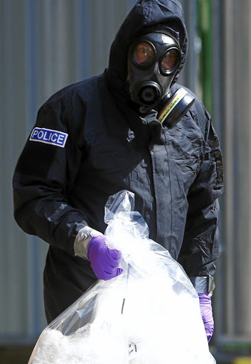 A forensic investigator, wearing a protective suit, emerges from John Baker House, after it was confirmed that two people were poisoned with the nerve-agent Novichok in Amesbury, on July 6 2018. Picture: REUTERS/HENRY NICHOLLS