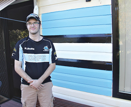 Narrabri local and Cronulla Sharks fan Corey Robinson in front of the strip he painted on the front of his house in support of the Sharks.