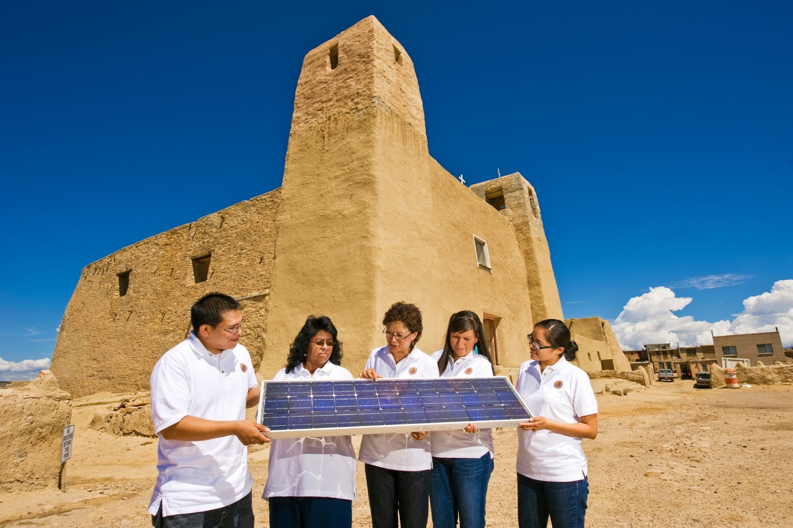 A group of Native energy professionals view a solar panel.