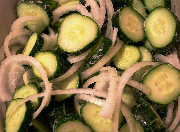 Combine cucumbers, onions, salt and ice in a large bowl. Mix well. Put a...