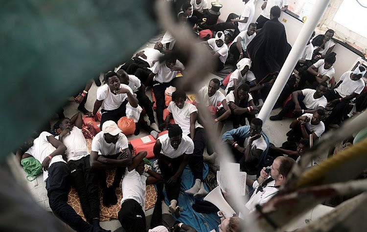 Migrants sit on the deck of the MV Aquarius, a rescue ship operated by SOS Méditerranée, in the central Mediterranean Sea, June 12 2018. Picture: REUTERS