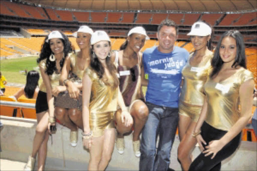 BEVY oF BEAUTIES: Former Bafana Bafana player Mark Fish is flanked by Miss World contestants during their visit to Soccer City ahead of the Miss World finals at Sun City on Saturday. Pic: VATHISWA RUSELO. 06/12/2009. © Sowetan.