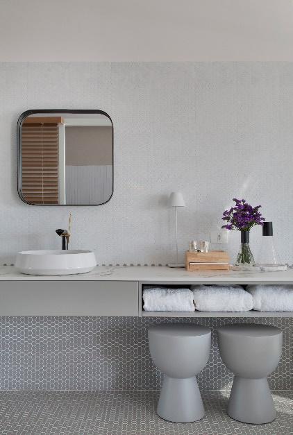 Lavabo em tons branco e cinza, pastilhas em formato hexagonal no piso e meia parede, bancos cinza e louças branca.