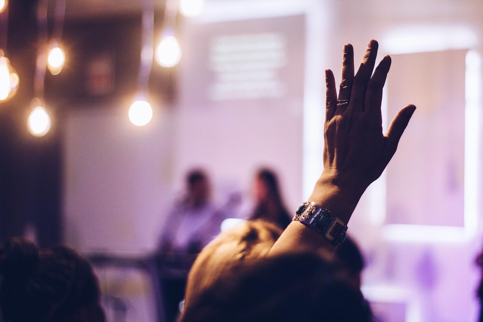 Pessoa levantando a mão em uma conferência